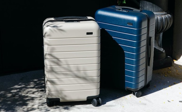 A pair of suitcases, one navy blue and one light gray, on a sidewalk.