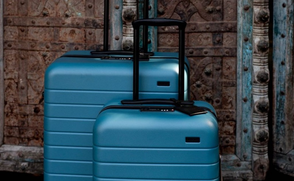 A small teal-blue suitcase and a bigger teal-blue suitcase next to each other, in front of a brown metal wall.