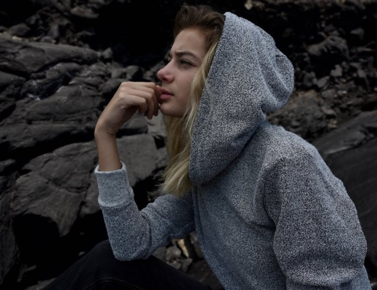 A woman is sitting against a rock background with her hand on her chin, wearing a gray hoodie with the hood up.