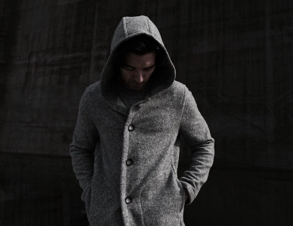 A man is wearing a gray hoodie with the hood up, standing against a dark background with his head lowered to look at the ground.
