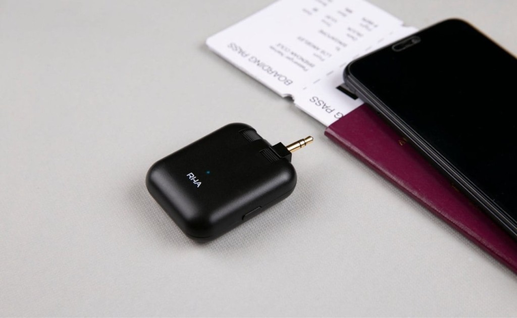 A small black transmitter is sitting next to a phone and plane tickets.
