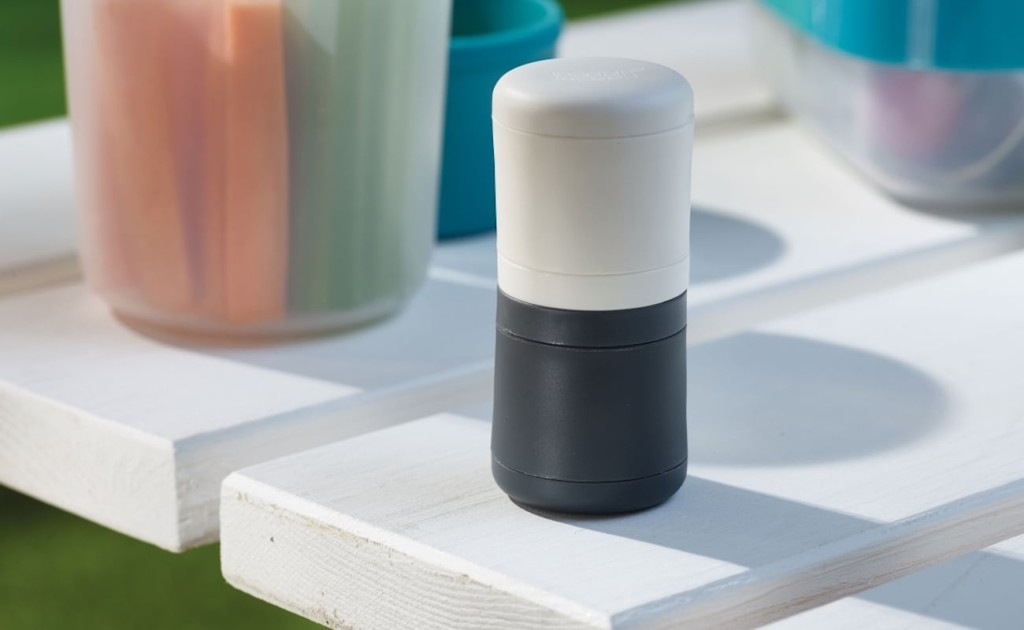 Black and white salt and pepper shakers are stacked together on a white tile.