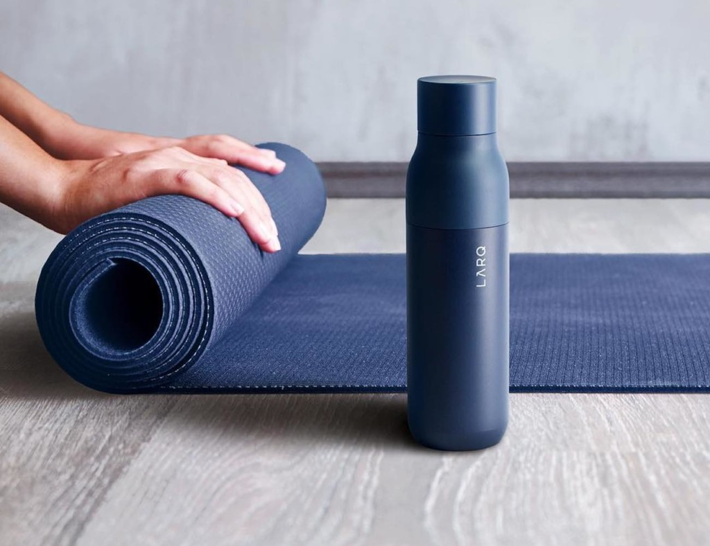 A navy-blue water bottle is sitting on the floor next to a navy-blue yoga mat that someone is rolling up.