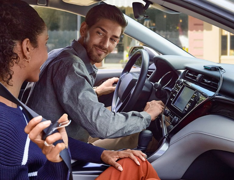 A man starting his car and looking at the passenger, and there is an Amazon Alexa on the dash for his car this winter.