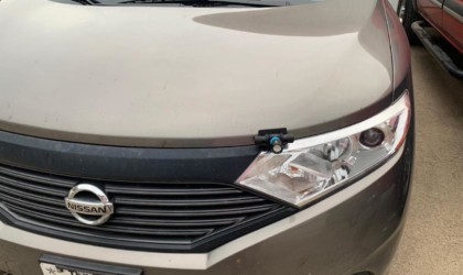 A tan sedan with a small light for the car this winter attached above the headlight.