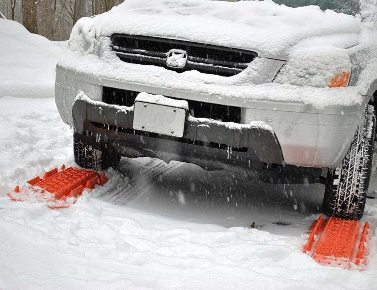 A small white SUV in the snow with orange traction mats for the car this winter under the front tires.