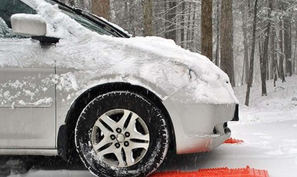 A side view of a silver SUV with orange tractions mats for the car this winter under the front tires.