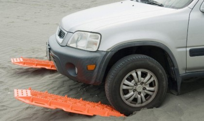 A small white SUV in the sand with orange traction mats for the car this winter under the front tires.