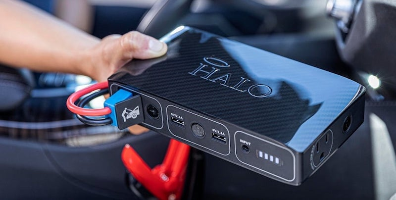 A hand holding a small portably jump starter for the car this winter.