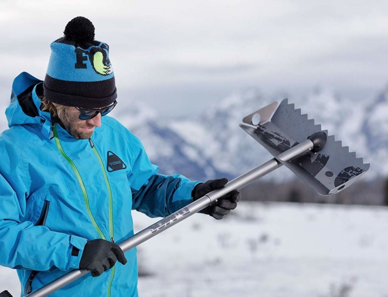 A man in a bright blue coat holding a shovel for the car this winter.