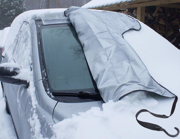A windshield cover for the car this winter that is halfway pulled off a windshield to reveal a clean window.