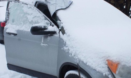 A car covered in snow, the door open to show the inner flap of a windshield cover for the car this winter.