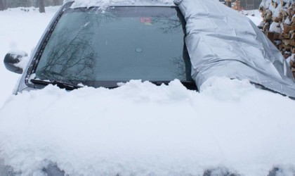 A small car that is covered in snow and has a windshield cover for the car this winter that is pulled mostly away to show a clean windshield.