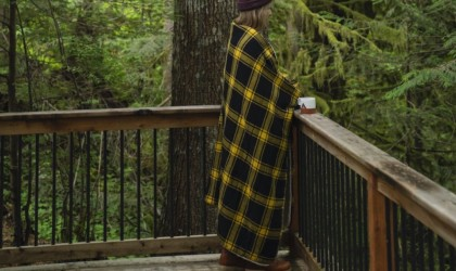 A woman standing on a deck and drinking from a mug with a black and yellow blanket for the car this winter wrapped around her shoulders.