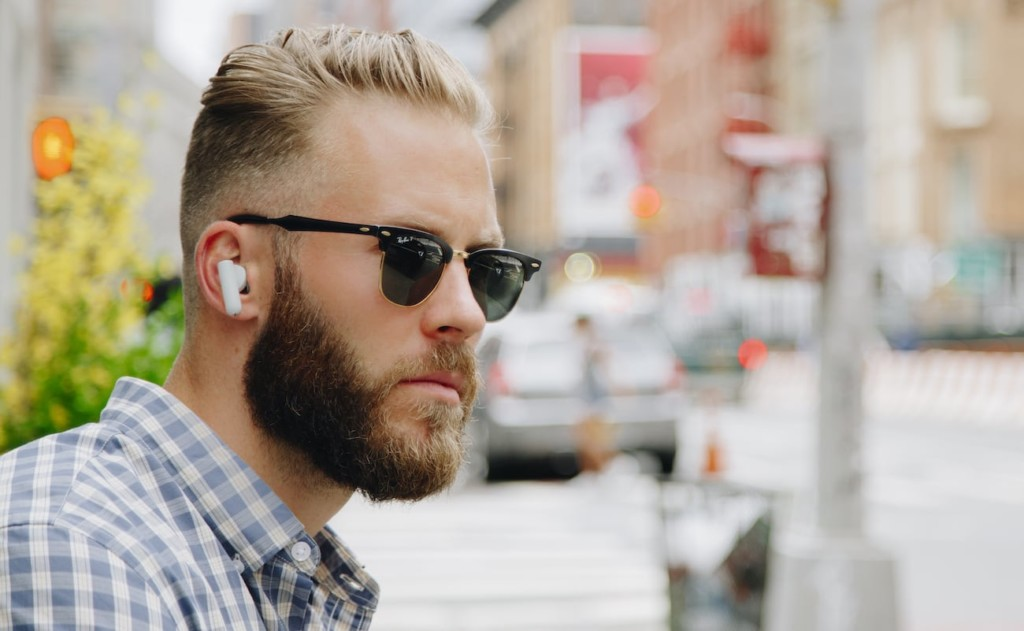 A side view of a bearded man in sunglasses wearing a pair of comfortable earbuds.