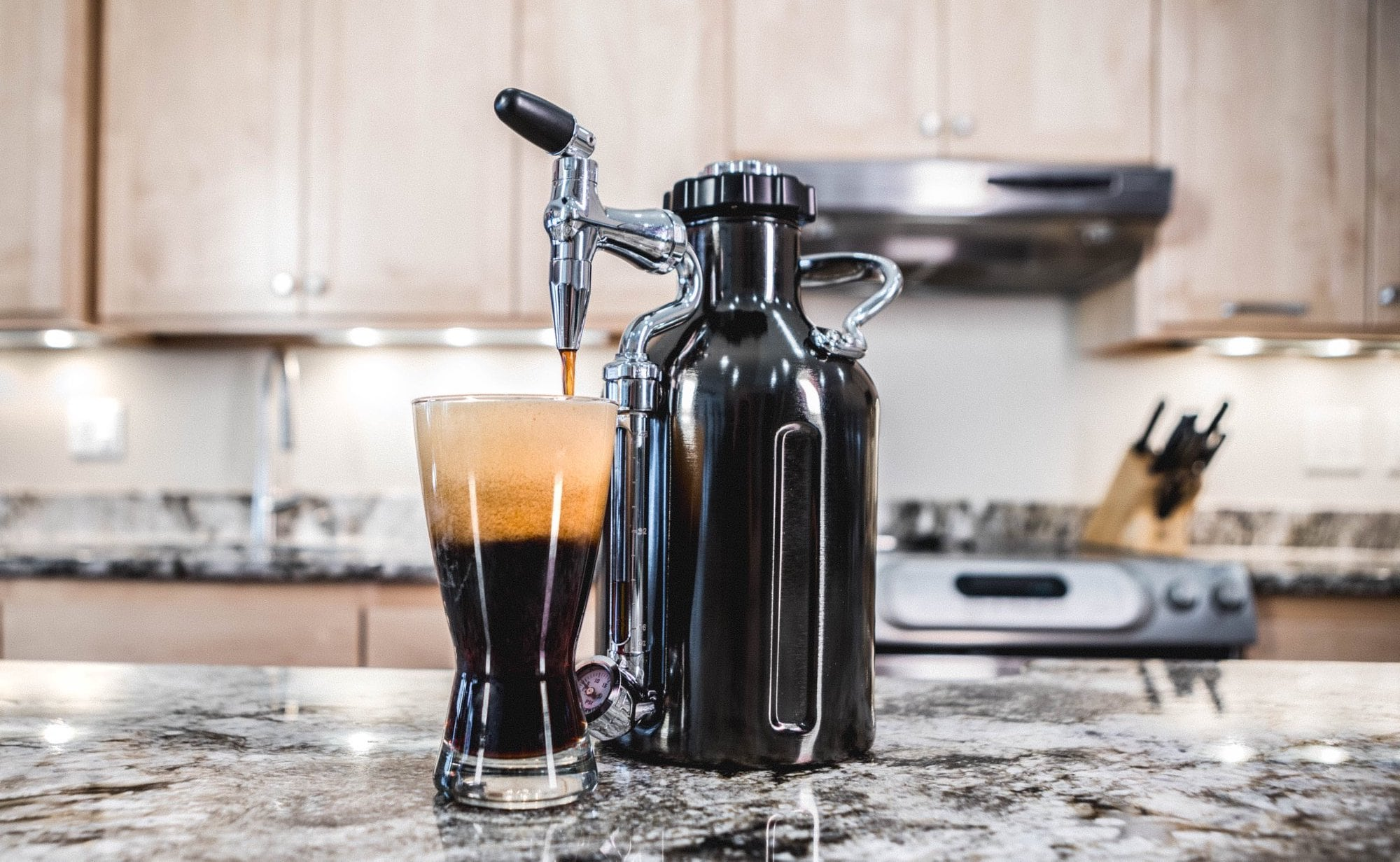 The cold brew coffee machine is on a kitchen counter and dispensing nitro coffee.