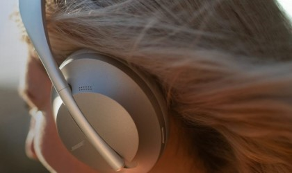 A close up of a silver pair of ANC headphones on a blonde woman's head.