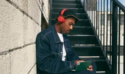 A man sitting on steps, wearing a pair of red ANC headphones.