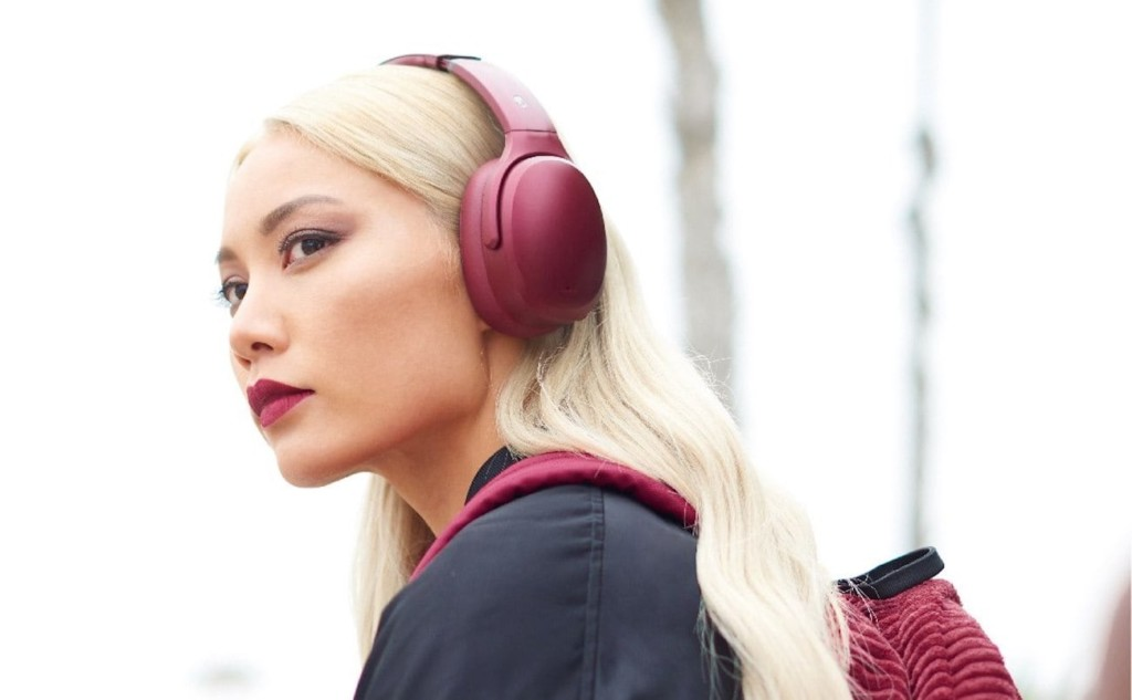 A blonde woman wearing a pair of dark red ANC headphones.