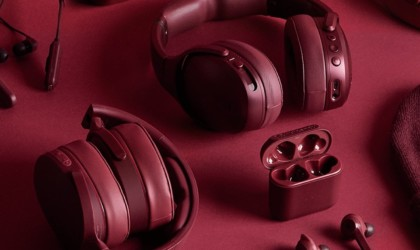 A pair of deep red ANC headphones, a matching case, and other accoutrements on a matching background.