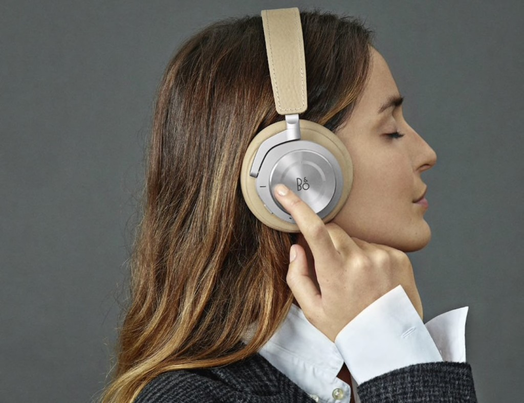 Side view of a brunette woman wearing silver and tan ANC headphones and pressing the side of an ear cup with one finger.