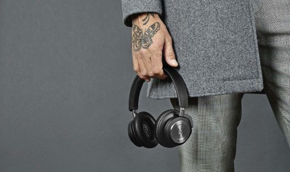 A man's hand holding a black pair of ANC headphones at his side.