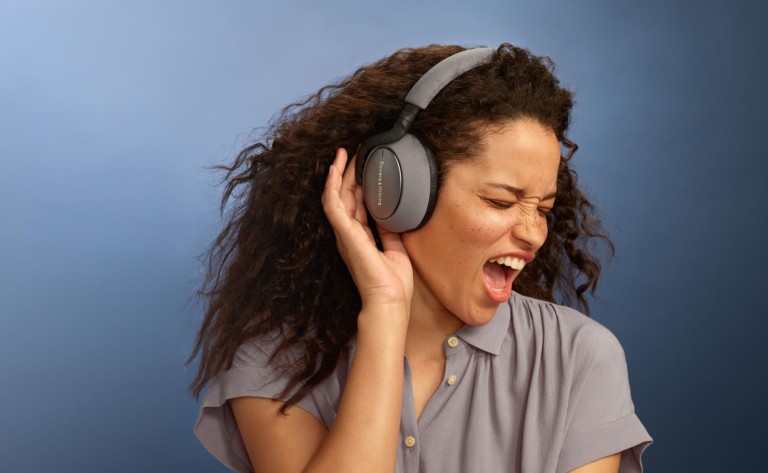 A woman singing and cupping her ear while wearing a pair of gray ANC headphones.