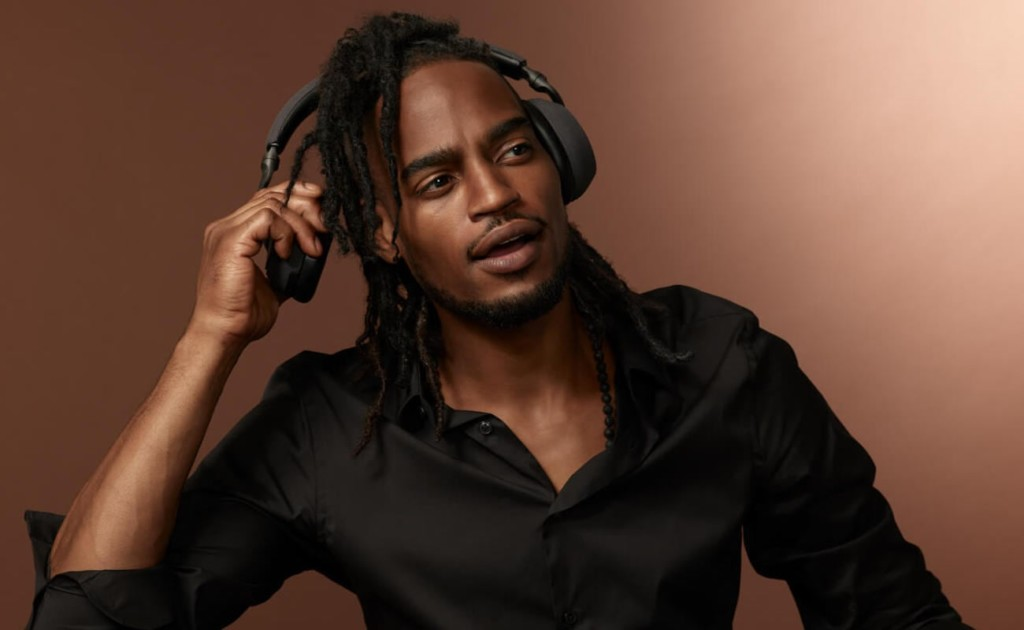A man wearing black ANC headphones and lifting the ear cup of one.