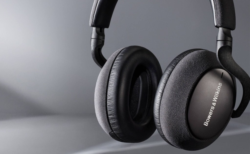 A close up of a pair of dark gray ANC headphones against a light gray background