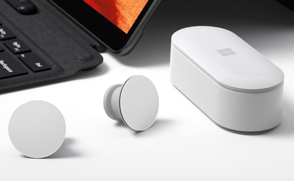 A pair of round white earbuds on a white table next to a white earbud cause and a black laptop.