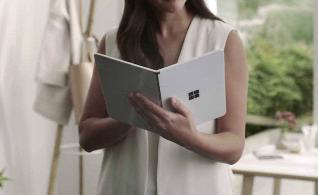 A woman is holding an impressive new technology, a white tablet, open like a book.