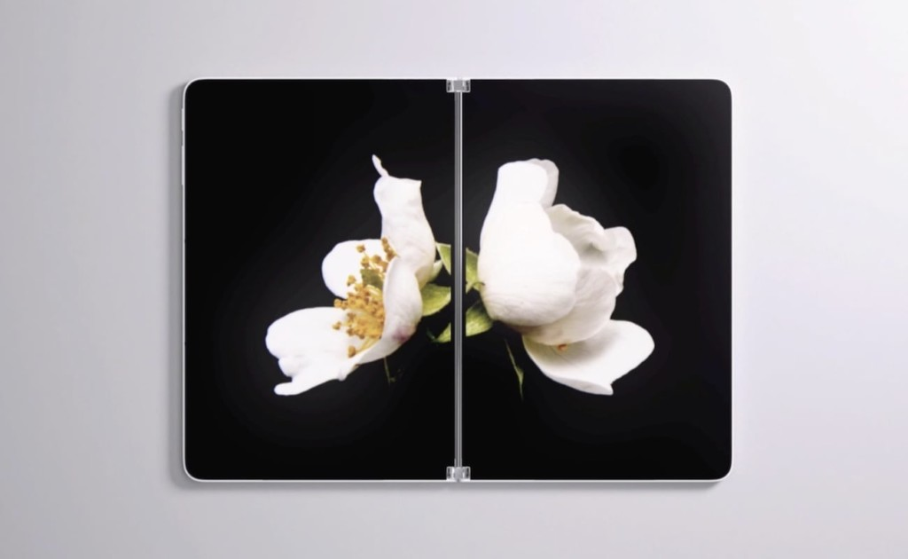 A tablet is open to show two side-by-side screens with a black background and a white flower on them.