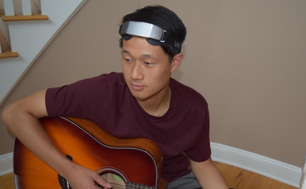 A man is wearing a neurostimulator headband and playing a guitar.