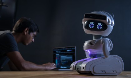 A small white robot is on a table while a man works on a laptop in the background.