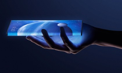 A hand is holding a glowing smartphone with a wrap-around screen in their hand