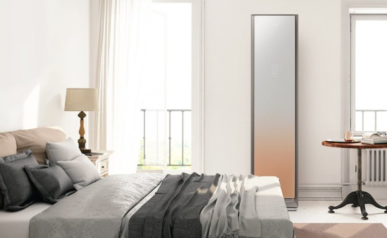 A tall, slim dry-cleaning cabinet is in a bright bedroom next to a bed.