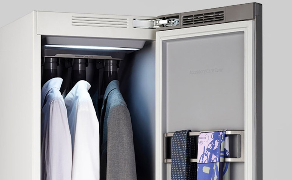 A dry-cleaning closet is open to show ties and suit jackets hanging inside.