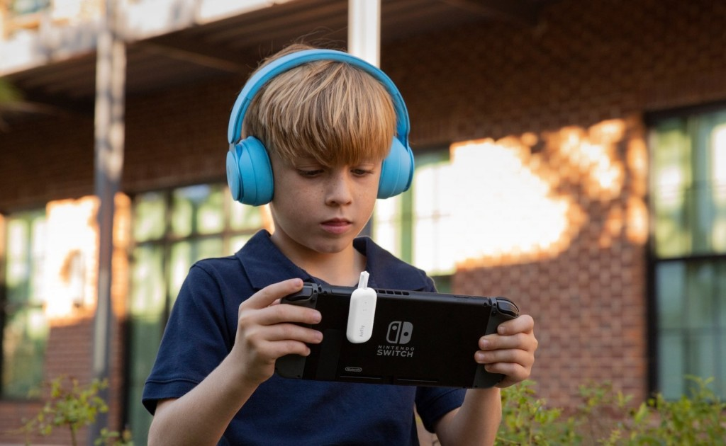 A little boy is wearing light blue headphones and holding a black video game device.