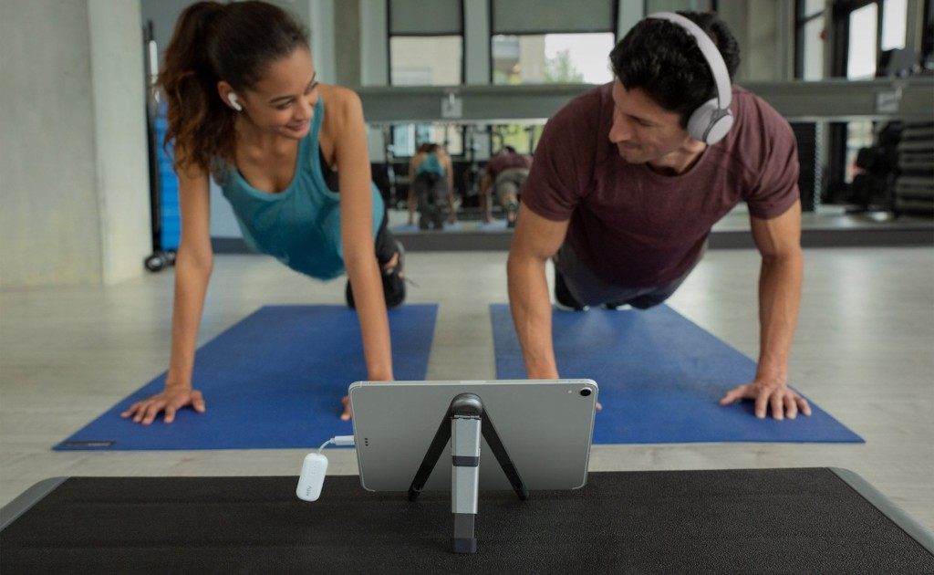 A man and a woman are on yoga mats in the plank position, and there is a tablet in front of them on the floor.