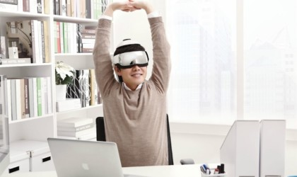 A person is sitting behind a desk, stretching their arms up and wearing a massage helmet