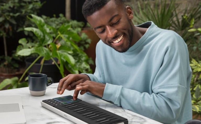 A man in a light blue sweater is smiling and pressing a button on a black music keypad.