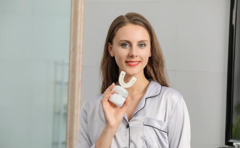 A woman is smiling and holding a toothbrush device.