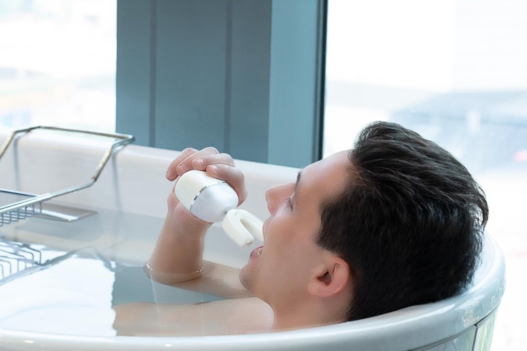 A man is in a bathtub and putting a toothbrush device into his mouth.