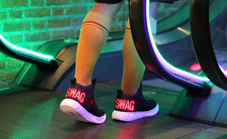 """A person about to get on an escalator and wearing tennis shoes that say """"swag"""" in red lights on the back."""