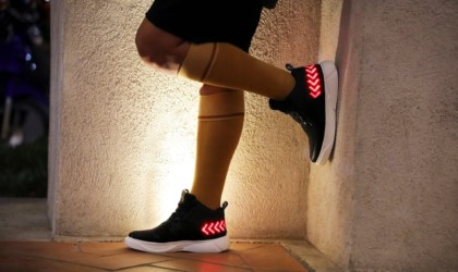 A person is standing with one foot resting on the wall, wearing black sneakers that have red arrow on them in lights.