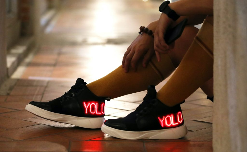 """A person is wearing black tennis shoes that say """"YOLO"""" in red lights."""