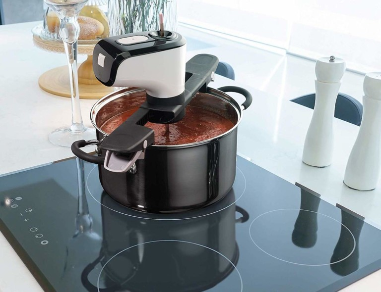 A pot is on a stove and it has a self-stirring device on the top of it.