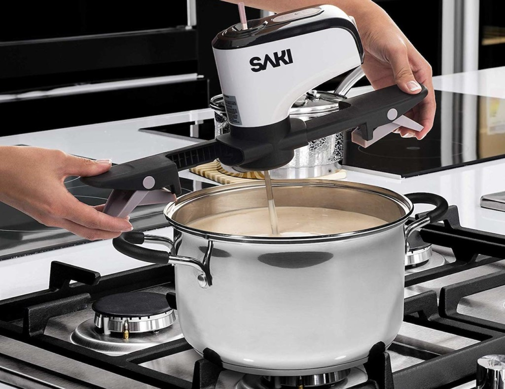 A pair of hands is placing a self-stirring kitchen device into a pot.