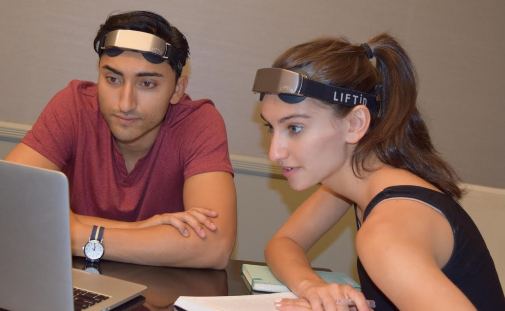 A man and a woman, each wearing a brain stimulation device headband and looking at a laptop.