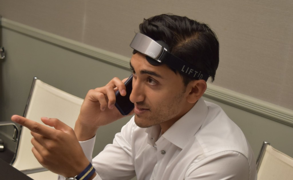 A man talking on the phone while wearing a brain stimulation device headband.